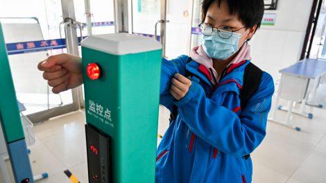Estudante universitário medindo temperatura na entrada da universidade em um totem