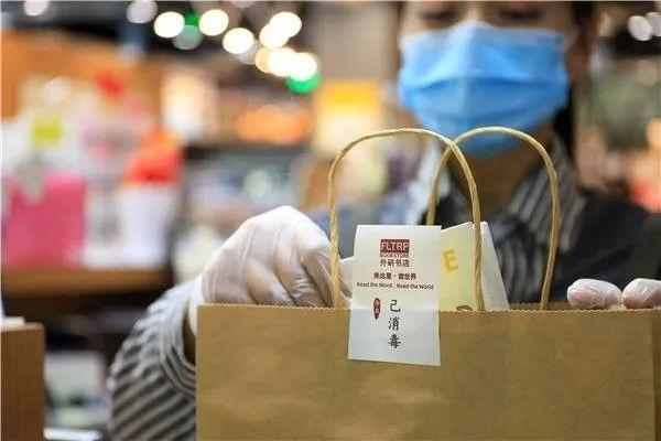 Vendedora com máscara colocando compra em uma sacola de papel