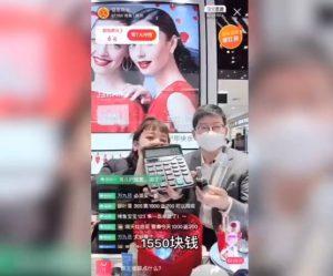 Printscreen de uma tela de celular de uma live com um homem e uma mulher segurando uma calculadora