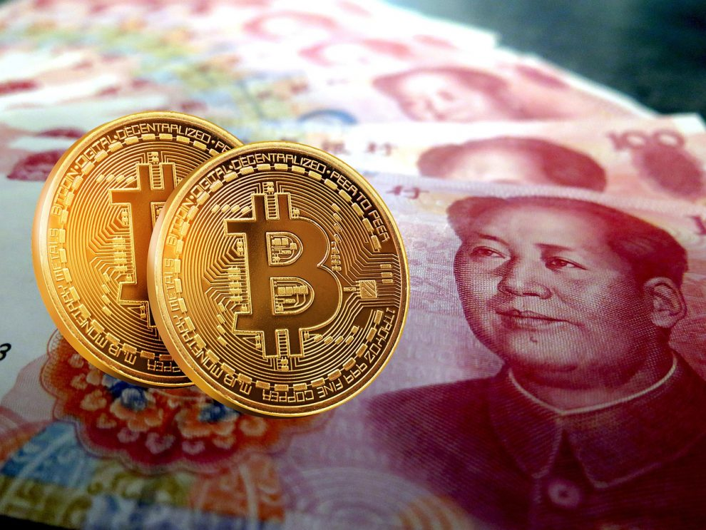 Duas moedas de bitcoin e cédulas da moeda chinesa Yuan Renminbi